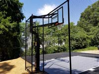 Highlight on hoop and rebound fence with black and grey home basketball court in Wellesley, MA.