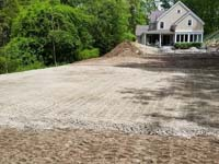 Yard in early phase of preparing the base for installation of black and grey basketball court in Wellesley, MA.