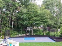 Finished view of graphite and light blue basketball court in West Bridgewater, MA, picturesque in the finished landscape and tree-laded suburban backdrop.