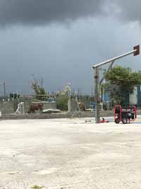 Replacement tennis and basketball courts in Codrington, Barbuda, courtesy of Australia, the Red Cross, and community effort, part of the ongoing recovery from hurricane Irma. Shown here, setting up to remove defunct goal post.